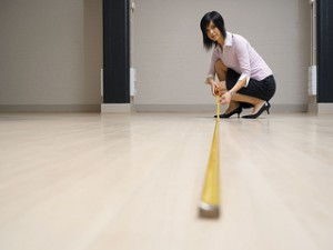 Young Woman In Large Room Measuring Floor With Tape Measure